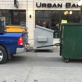 truck towing a green bin